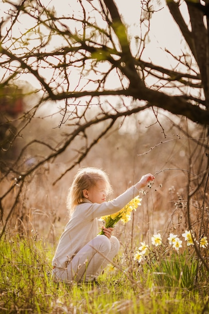 Cute blonde happy little girl with yellow daffodils in the spring country Premium Photo