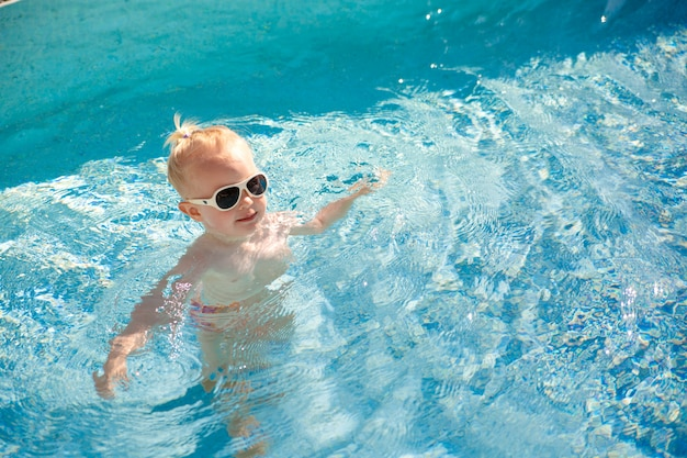Cute blonde little baby with sunglasses splashing happily in the pool with clear blue water. Premium Photo