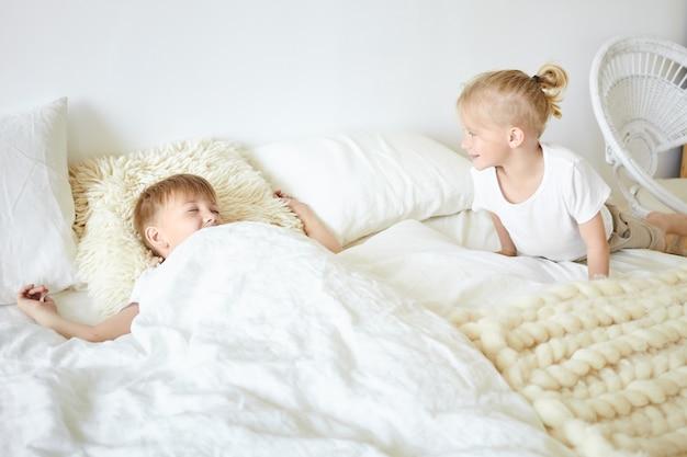 Симпатичный белокурый маленький мальчик в пижаме, сидящий на большой белой кровати, просыпается своего старшего брата, который спит рядом с ним, говоря «доброе утро». два брата вместе играют в спальне, веселятся Бесплатные Фотографии