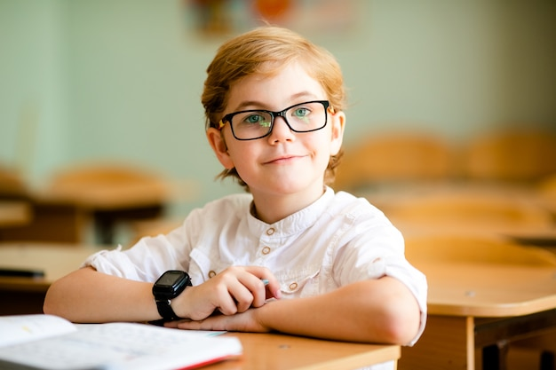 Cute blonde school student with stylish glasses writing in classroom Premium Photo