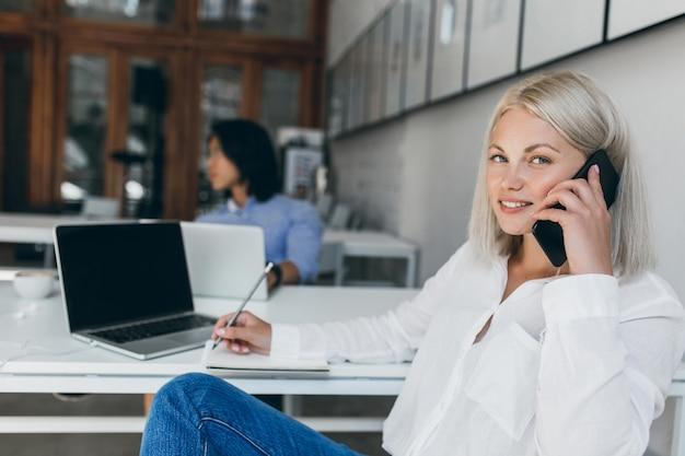 전화 통화 하 고 노트북에 데이터를 쓰는 흰 블라우스에 귀여운 금발 비서. 리셉션 데스크에서 우아한 아가씨와 함께 장발 아시아 It 전문가의 실내 초상화. 무료 사진