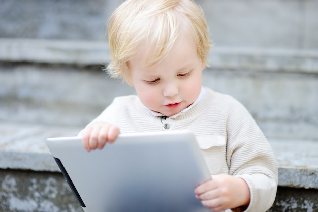 Cute blonde toddler boy playing with a digital tablet outdoors Premium Photo
