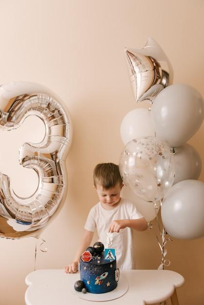 3歳のかわいい男の子が彼の誕生日を祝って、おいしい美しいケーキを食べています、風船を持った子供の写真 Premium写真