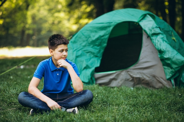 Cute boy camping in forest Free Photo