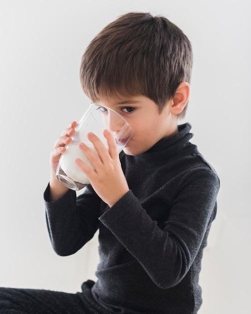 Cute boy drinking glass of milk Free Photo