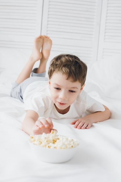Cute boy eating popcorn sitting in bed with white linens Premium Photo