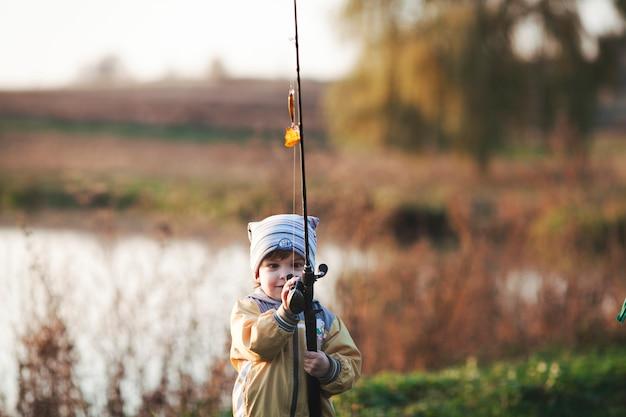 Cute boy fishing near lake Free Photo