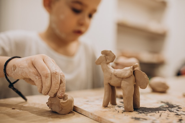 Cute boy forming toys from clay Free Photo