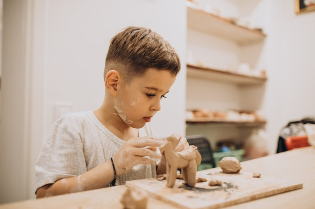 Ragazzo sveglio che forma i giocattoli dall'argilla Foto Gratuite