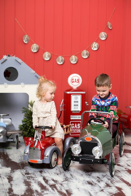 Cute boy and girl play and ride on toy cars. happy childhood Premium Photo