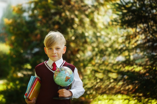 Cute boy going back to school. child with books and globe on first school day Premium Photo