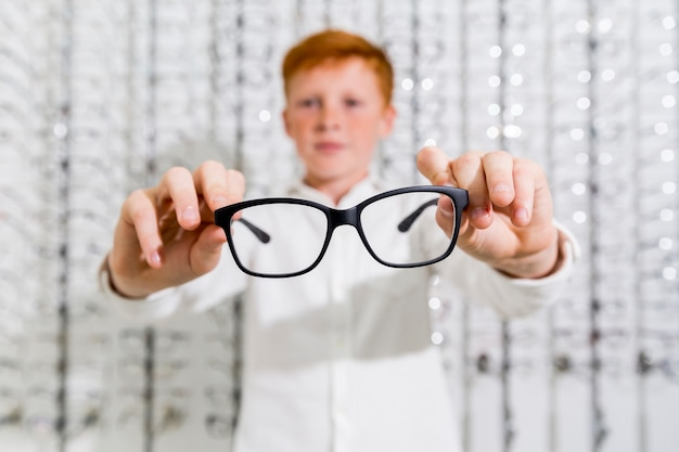 Cute boy holding black spectacle in optics store Free Photo