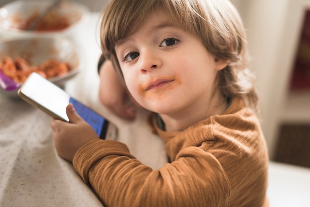 Cute boy holding phone at table Free Photo