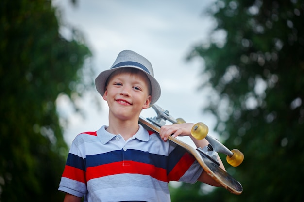 Cute boy holding skateboard  in hand outdoors.wearing cap and stylish clothes Premium Photo