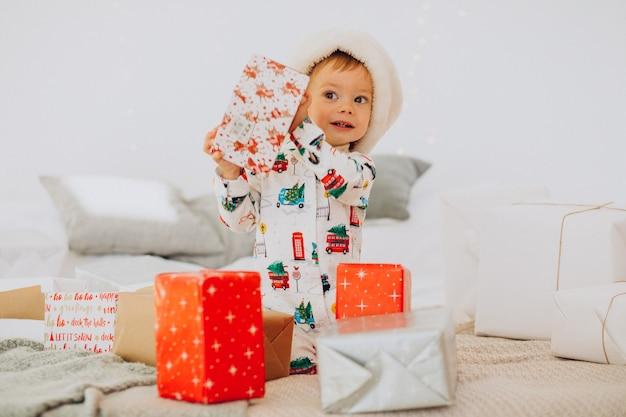 Милый мальчик в новогодней шапке открывает подарки на рождество Бесплатные Фотографии