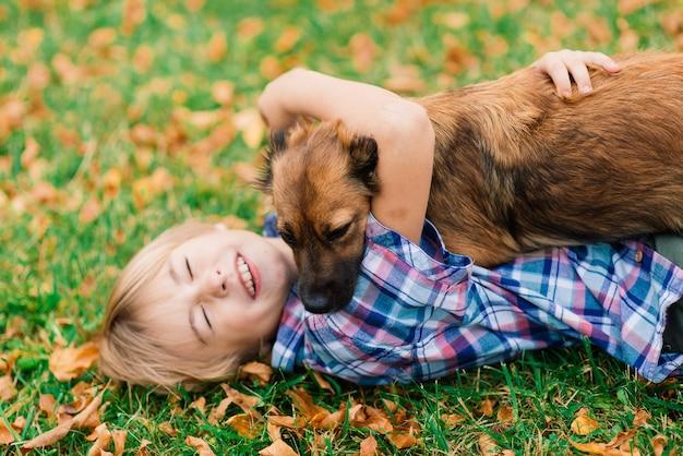 Милый мальчик играет и гуляет со своей собакой на лугу. Premium Фотографии