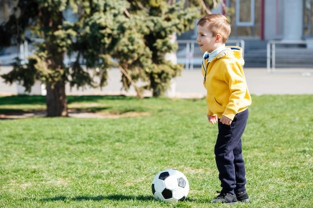 Милый мальчик играет в футбол в парке Бесплатные Фотографии