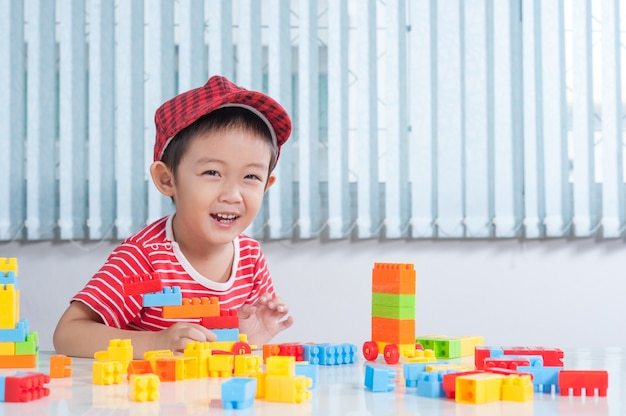 Cute boy playing with colorful plastic bricks at the table in the children's room