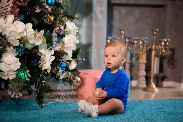 Cute boy sitting on the carpet near christmas tree Premium Photo