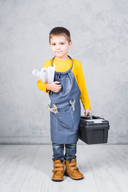 Cute boy standing with tool box and paper rolls Free Photo
