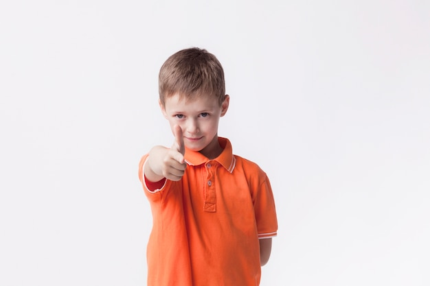 Cute boy wearing orange t-shirt pointing at camera on white wall Free Photo