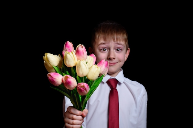 Cute boy in white shirt gives a bouquet of tulips. isolate Premium Photo