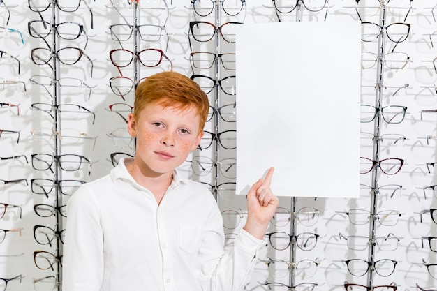 Cute boy with freckle on face pointing at black white paper in optics shop Free Photo