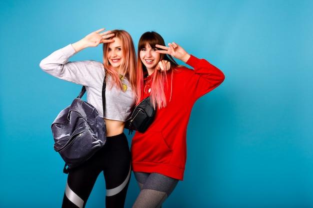 Милый яркий портрет двух счастливых симпатичных хипстерских девушек в спортивной одежде для фитнеса и рюкзака, улыбок и объятий, синяя стена. Бесплатные Фотографии