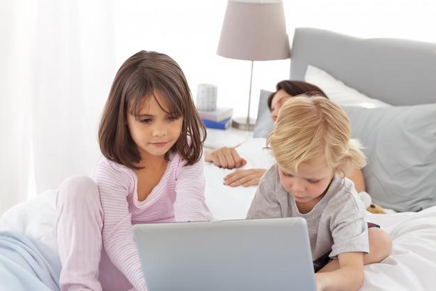 母親が寝ている間、かわいい兄と妹がインターネットにいる Premium写真
