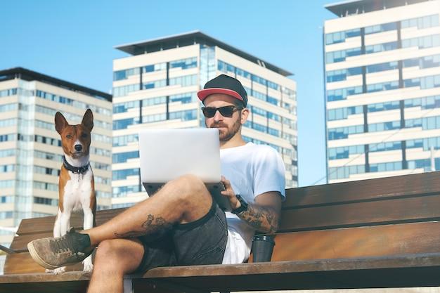 都市公園でラップトップに取り組んでいる飼い主の隣に座っているかわいい茶色と白の犬 無料写真