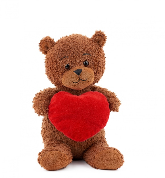 Cute brown teddy bear holding a big red heart Premium Photo