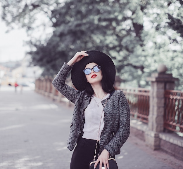 Cute brunette with red lips in hat and sunglasses posing in city Premium Photo