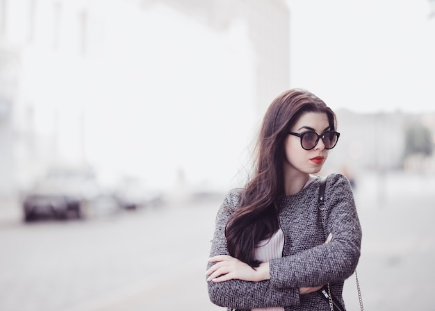 Cute brunette with red lips in sunglasses posing in city Premium Photo