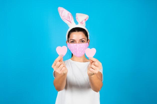 Симпатичная брюнетка женщина с бумажным сердцем, изолированным на синем Premium Фотографии