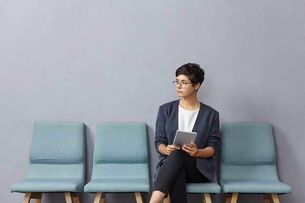 Cute businesswoman looks pensively aside, waits meeting with partners Free Photo