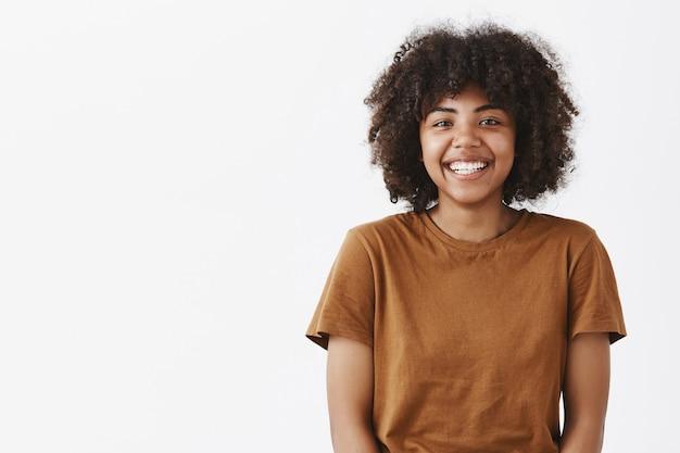 Милая беззаботная дружелюбная афроамериканская девочка-подросток с афро-прической широко улыбается, застенчиво и радостно встречает новых одноклассников Бесплатные Фотографии