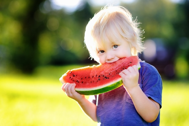 Cute caucasian little boy with blond hairs eating fresh watermelon outdoors Premium Photo