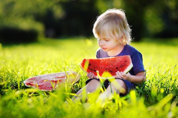 Cute caucasian little boy with blond hairs eating fresh watermelon outdoors Premium Photo