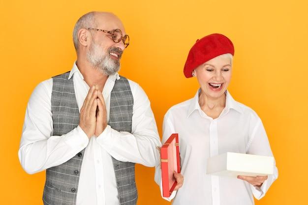 생일에 남편의 선물로 상자를 여는 동안 흥분에 입을 여는 세련된 모자에 귀여운 매력적인 중년 여성, 기쁨으로 손을 문지르는 수염 난 수석 남자 무료 사진