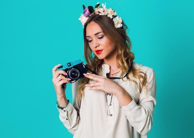 明るい青色の背景に写真を撮る春のスタイリッシュな服でポーズをとって頭にフローラルリースとかわいい陽気な金髪の新鮮な女性。柔らかいフローラルリース、春の服を着ています。 無料写真