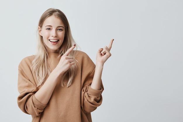 かわいい陽気な金髪の若い女性が広く笑みを浮かべて指を離れて指して、面白いと刺激的な何かを示す 無料写真