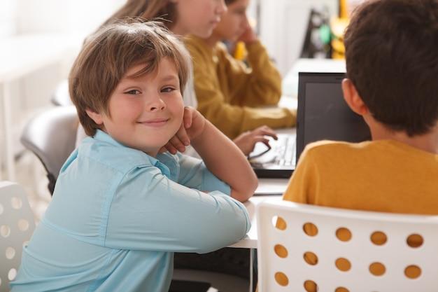 コンピュータ学校でクラスメートと一緒に勉強しながらカメラに微笑んでいるかわいい陽気な男の子 Premium写真