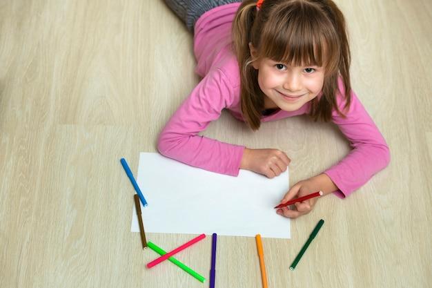 白い紙にカラフルな鉛筆クレヨンで描くかわいい子少女。美術教育、創造性の概念。 Premium写真