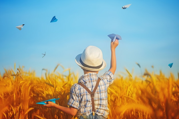 Cute child holding in hand paper airplane in the wheat golden field on a sunny summer day. Premium P