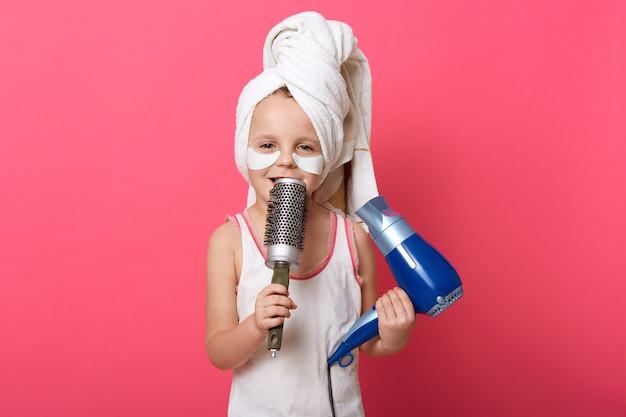 Cute child imagines she is super star and singing with comb in hands Free Photo