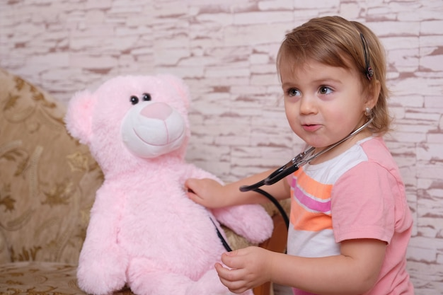 Cute child playing doctor or nurse with plush toys at home. Premium Photo