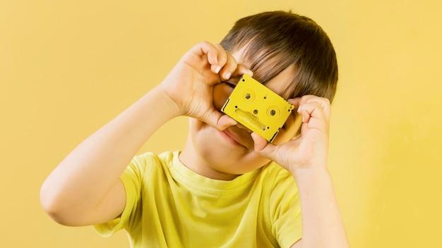 Bambino sveglio che gioca con un vecchio nastro di casette Foto Gratuite