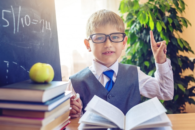 Cute child sitting at the desk in the classroom. boy discover important information during a lesson Premium Photo