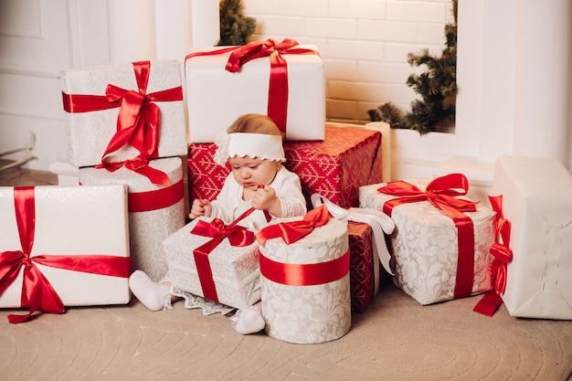 Cute child in white dress posing under christmas tree. Premium Photo
