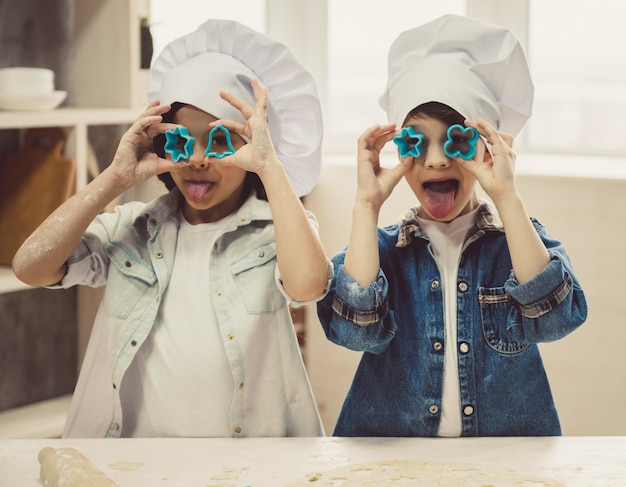 Cute children in chef hats are playing with cookie. Premium Photo
